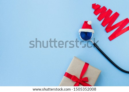 Medical stethoscope in a red Santa Claus hat, gift box and christmas tree made from red ribbon on a light blue background. Christmas and New Year concept. Creative medical winter background, postcard #1505352008