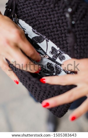 girl undoes the inside pocket of a handbag. A small black knitted handbag in the hands of a young girl in a blue dress. Beautiful handmade accessory. Clutch on cotton strap #1505383643