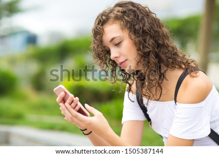 Beautiful young girl using a mobile phone at the park.