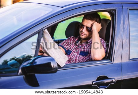 Bad navigation. Young man having a problem with orientation on the road during his journey with a car. He looking at map and try to find the missed road. Traveling and transportation concept #1505414843