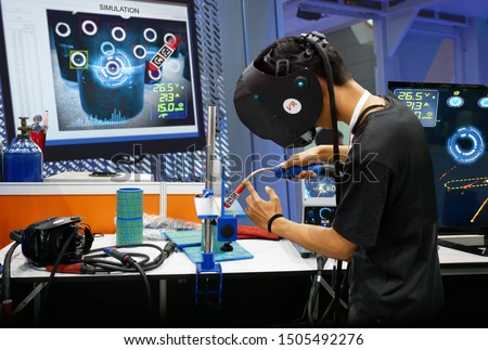 Virtual reality technology in Steel industry 4.0. Man wearing VR glasses to see simulate welding steel pipe for training, measurement and analytic to monitor screen in smart factory. #1505492276