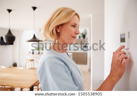 Close Up Of Mature Woman Adjusting Central Heating Temperature At Home On Thermostat #1505538905