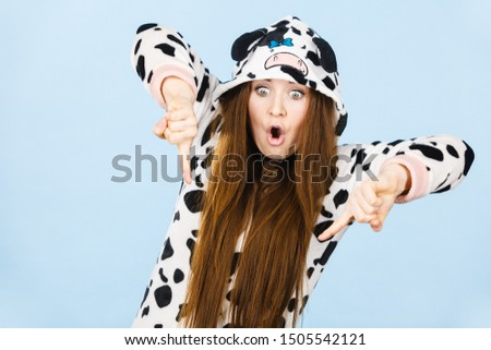 Happy teenage girl in funny nightclothes, pajamas cartoon style pointing down with positive surprised face expression, studio shot on blue. Advertisement concept