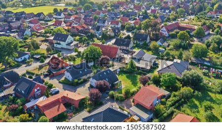 Aerial view of a suburb with detached houses, garden areas, lawns and a close neighbourhood