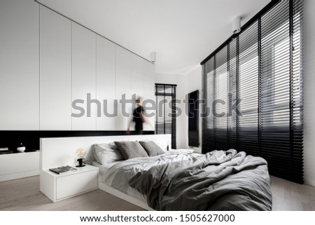Luxury bedroom interior in black and white and woman walking in it #1505627000