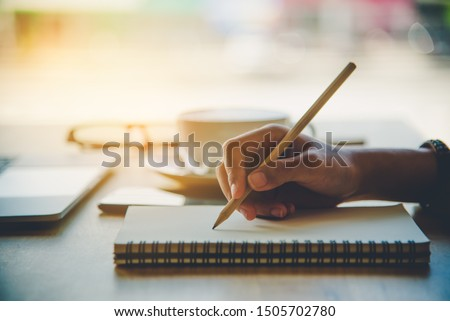 Closeup of woman's hand writing on paper Royalty-Free Stock Photo #1505702780