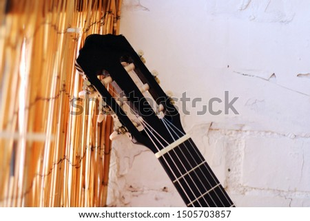 Music Concept: Brown acoustic guitar on a white wall. #1505703857