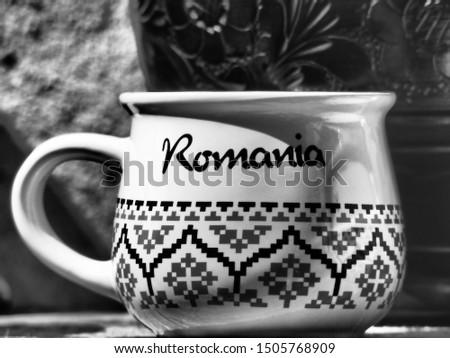 Rasnov/Romania - August 13 2019: Souvenir ceramic cup with the word Romania written on it at the Rasnov citadel, Romania. BW filter applied #1505768909