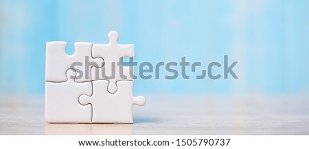 puzzle pieces on wood table background. solutions, mission, successful, goals, cooperation, partnership and strategy concept Royalty-Free Stock Photo #1505790737