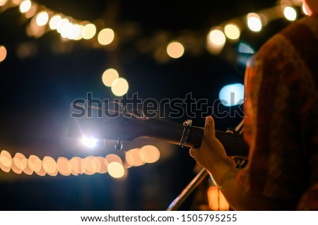 Man play acoustic guitar at outdoor concert with a microphone stand in the front, musical concept. Royalty-Free Stock Photo #1505795255