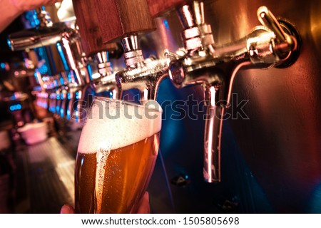 Bartender pouring a large lager beer in tap. Bright and modern neon light, males hands. Pouring beer for client. Side view of young bartender pouring beer while standing at the bar counter. #1505805698