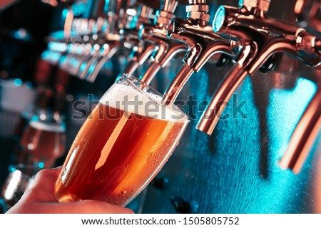 Hand of bartender pouring a large lager beer in tap. Bright and modern neon light, males hands. Pouring beer for client. Side view of young bartender pouring beer while standing at the bar counter. #1505805752