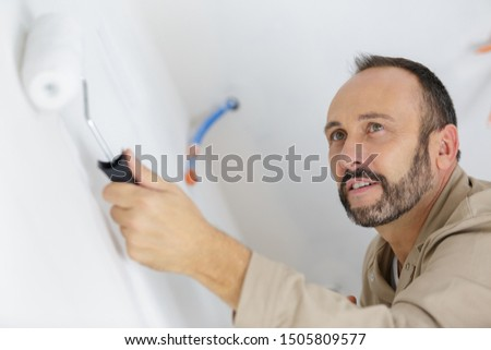 man holding a paint roller for painting #1505809577