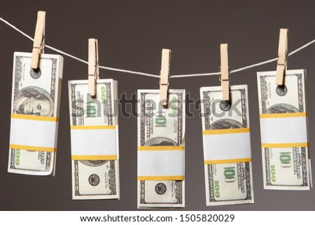 Bundles of money are drying on the rope. Money laundering. Financial crimes. Legalization of funds. Illegal activity. Financial monitoring Committee. Offshore.