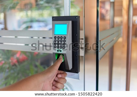 Yong man press down the finger on fingerprints scan machine to access the door security systems. Selective focused #1505822420