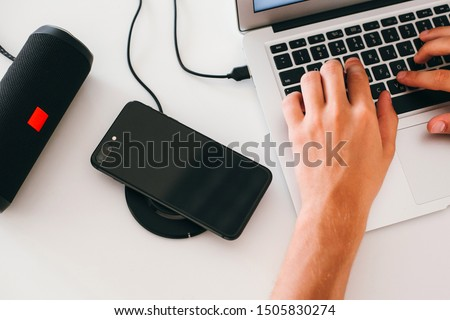 Man's hands working on laptop, wireless speaker and wireless phone charger #1505830274