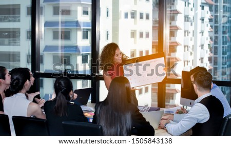 Businesswoman stands to meeting around board table have presenting to colleagues with planning and writing work or vacation on calendar planner.Writing plan on memo scheduled to vacation weekend.Share #1505843138