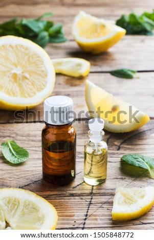 Essential lemon oil in bottle, fresh fruit slices on wooden background. Natural fragrances #1505848772