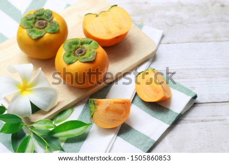 Persimmon fruits, slices and half  persimmons on wooden plate decorated with frangipani flower and green leaves on wooden  background #1505860853