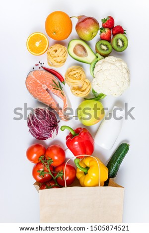 Healthy food background. Healthy food in paper bag fruits, vegetables, milk, pasta and fish on white background. Shopping food supermarket, meal and nutrition plan concept. Top view #1505874521