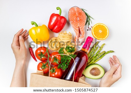 Shopping healthy food and female hands. Healthy food in paper bag fish, pasta, vegetables, fruits and wine on white background. Shopping food supermarket, healthy eating concept. Top view #1505874527