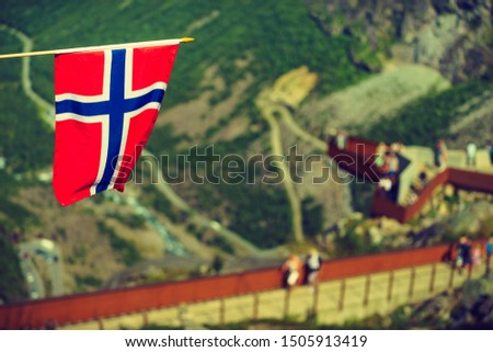 Trollstigen mountain road landscape in Norway, Europe. Norwegian flag waving and many tourists people on viewing platform in background. National tourist route. #1505913419