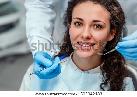 Young female patient sitting on chair in dental office. Preparing for dental exam. Looking at camera. #1505942183