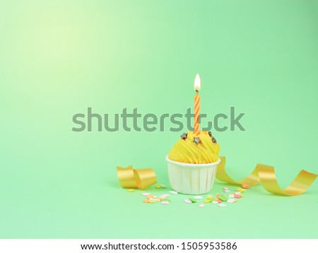 Sweet yellow cupcake with bow candle on green background with copy space. Happy birthday party background concept.  #1505953586