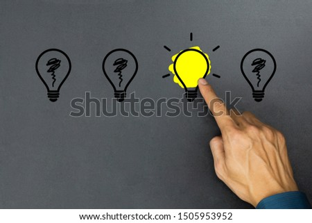 Creative ideas concept. Conceptual different thinking or leadership. A businessman hand choose a one shining light bulb and many light bulb goes out on blackboard. #1505953952