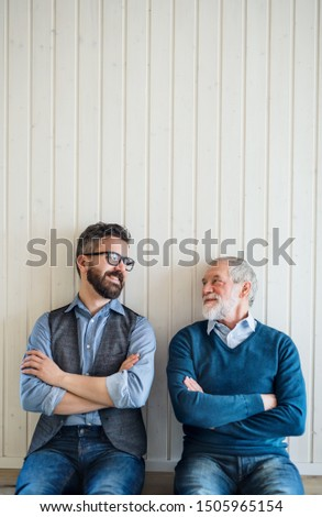 A portrait of adult hipster son and senior father sitting on floor indoors at home. #1505965154