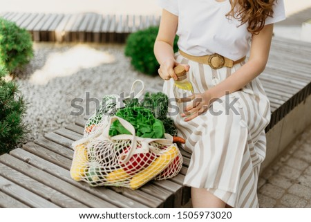 Zero waste concept with copy space. Woman holding cotton shopper and reusable mesh shopping bags with vegetables, products. Eco friendly mesh shopper. Zero waste, plastic free concept Royalty-Free Stock Photo #1505973020