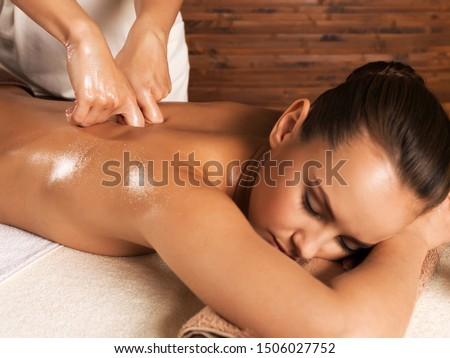 Photo of a beautiful young woman having back massage in spa salon.