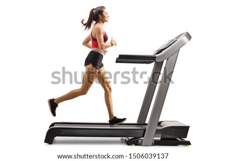 Full length profile shot of a young sporty female athlete running on a treadmill isolated on white background #1506039137