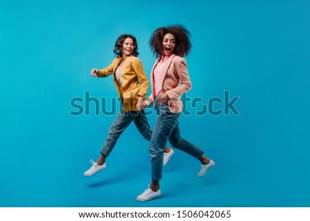 Joyful female models running on blue background. Full-length portrait of two stylish women in jeans. #1506042065