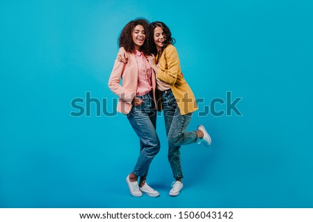 Cheerful latin woman in yellow jacket dancing in studio. Full length portrait of two trendy girls in white shoes. #1506043142