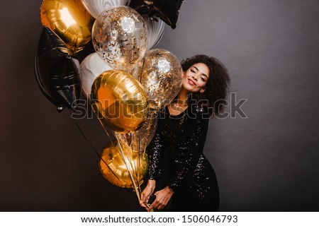 Romantic african girl holding bunch of party balloons. Indoor shot of graceful black lady celebrating birthday. Royalty-Free Stock Photo #1506046793