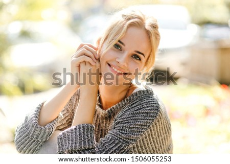 Nice girl in trendy oversized sweater leaned and looking at camera against background of cars with smile #1506055253