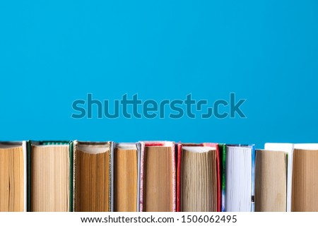 Simple composition of hardback books, raw books on wooden deck table and blue background. Stacking books without inscriptions, empty spine. Back to school. Open book. Place for text. #1506062495