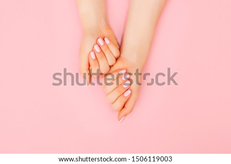 Hands of a beautiful woman on a pink background. Delicate hands with natural manicure, clean skin. Light pink nails. #1506119003