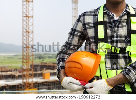 Close-up building construction worker holding helmet, construction safety concept