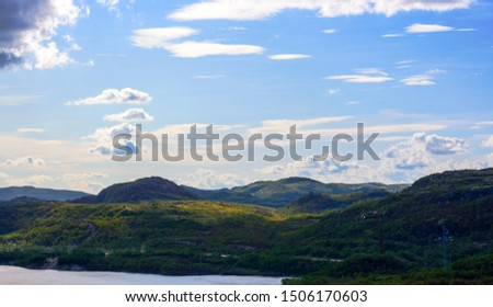 Green hills under a low, deep Northern sky and peacefull lake. These places in the Murmansk region are not far from Teriberka. Clouds fly over the trees and hills. Quiet and peaceful landscape #1506170603