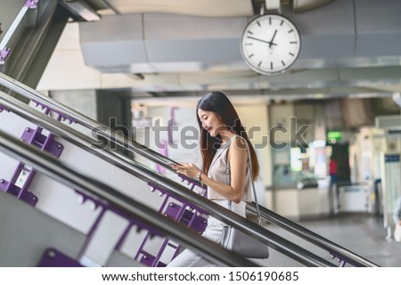 Young Asian woman passenger using smart mobile phone and walking up the stairs in subway station when traveling in big city,japanese,chinese,Korean lifestyle and daily life,commuter and transportation #1506190685
