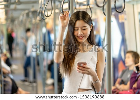 Young Asian woman passenger using social network via smart mobile phone in subway train when traveling in big city,japanese,chinese,Korean lifestyle and daily life, commuter and transportation concept #1506190688