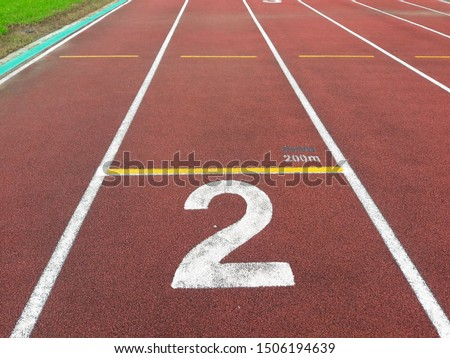 The number at start point of running track or athlete track in stadium (2). Running track is a rubberized artificial running surface for track and field athletics.  #1506194639