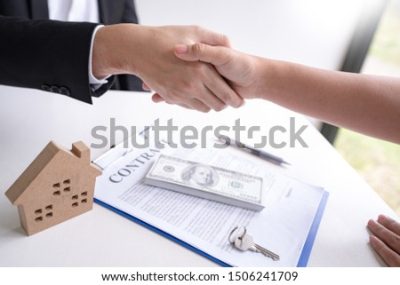 Customer and broker shake hands agreeing to buy new house at meeting after making sale purchase deal or finish buying or rental real estate with agent, Success deals concept. #1506241709