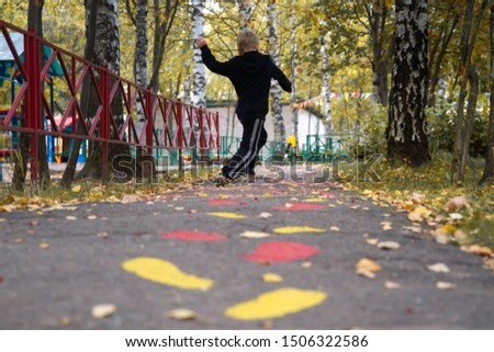 The boy runs on the tracks on the pavement. Traces of paint on t #1506322586
