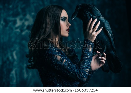 A witch in hat and dress with a raven. Halloween. Celebration. Royalty-Free Stock Photo #1506339254