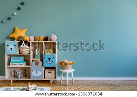 Stylish scandinavian newborn baby room with wooden cabinet, toys, children's chair, natural basket  Modern interior with eucalyptus background walls, wooden parquet and cottona balls. Home decor. #1506371084