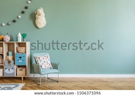 Stylish scandinavian newborn baby room with wooden cabinet, toys, children's armchair and pillow. Modern interior with eucalyptus background walls, wooden parquet and cotton balls. Cute home decor. #1506371096