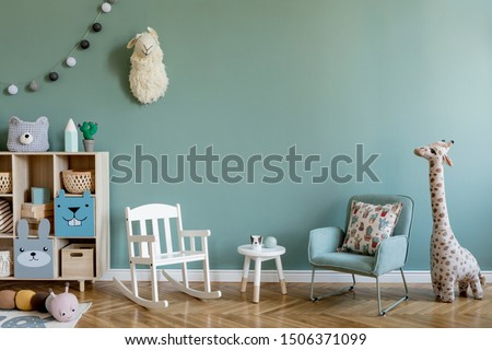 Scandinavian interior design of playroom with wooden cabinet, armchairs, a lot of plush and wooden toys. Stylish and cute childroom decor. Eucalyptus background walls. Copy space.  Template.